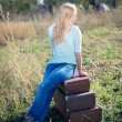 Girl sitting on suitcases — Stock Photo #58536153