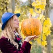 Portrait of holding pumpkin elegant beautiful blond young hipster woman having fun happy smiling and looking at camera on autumn copy space outdoors background — Stock Photo #58536193
