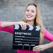 Woman holding cinema clapper board — Stock Photo #58536349