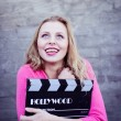 Woman holding cinema clapper board — Stock Photo #58536353