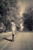 Lady on autumn road — Stock Photo