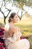 Woman sitting on hay — Stock Photo