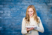 Image of beautiful blond young lady in white wool sweater using tablet pc at blue concrete wall copy space background — Stock Photo
