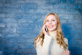 Image of beautiful blond young lady in white wool sweater speaking on mobile at blue concrete wall copy space background — Stock Photo