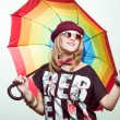 Studio portrait of teenage hipster girl wearing trendy hat and sunglasses with colorful umbrella over olive copy space background — Stock Photo #60348821
