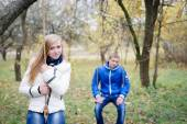 Happy teen couple outdoors on cold autumn day sitting on swings — Stock Photo