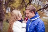 Happy teen couple outdoors on cold autumn day sharing apple — Stock Photo