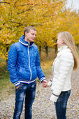 Happy teen couple walking outdoors on cold autumn day — Stock Photo