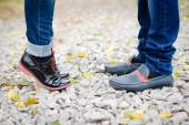 Teenage couple feet closeup in black leather shoes when reaching for kiss — Stock Photo