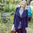 Young lady in retro overcoat with vintage suitcase waiting in autumn park copyspace background — Stock Photo #62288761
