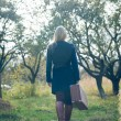 Young lady in retro overcoat with vintage suitcase waiting in autumn park copyspace background — Stock Photo #62288765