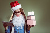 Girl in Christmas hat, glasses and beard santa holding a christmas balls and gifts — Stock Photo