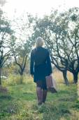 Young lady in retro overcoat with vintage suitcase waiting in autumn park copyspace background — Stock Photo