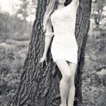 Pretty fashion girl leaning against big tree — Stock Photo #62417025
