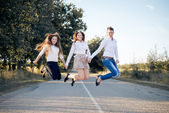 Young girls jumping on road — Stock Photo