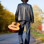 Man holding guitar and walking away — Stock Photo #80035364