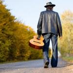 Man holding guitar and walking away — Stock Photo #80035582