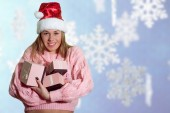 Smiling happy girl in santa hat with gift boxes — Stock Photo