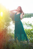 Lady in green dress posing by river — Stock Photo