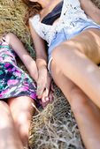 Two girlfriends lying on hay stack — Stockfoto