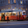 Постер, плакат: Red old trolley car in Vienna in the first District by night