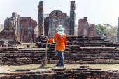 Worker at temple area in Ayutthaya climbing a stupa — Stock Photo