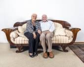 Senior  couple in love sitting on a sofa — Stock Photo