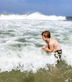 Boy enjoys the waves of the sea — Stock Photo