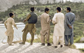 Pakistani men atKarakoram Highway in local dress watch the valle — Stock Photo
