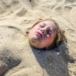 Young girl is covered by sand at the beach — Stock Photo #55908501