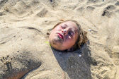 Young girl is covered by sand at the beach — Stock Photo