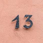 House number thirteen at a pink wall — Stock Photo