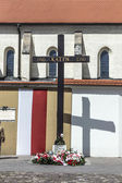 Cross of Katyn placed on the square in front of the church St. G — Stock Photo
