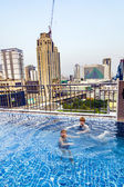 Boys swim in an open air pool with beautiful view to the skyscra — Foto de Stock