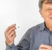 Hombre serio en camisa manejando su audífono — Foto de Stock