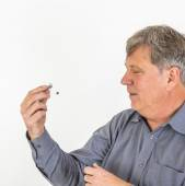 Serious man in shirt handling his  hearing aid  — Stock Photo
