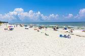 People enjoy the beautiful white beach at Naples Pier — Stock Photo