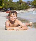Boy lies at the sandy beach and enjoys the fine warm sand — Stock Photo