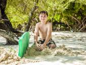 Happy young boy is digging in the sand of the beach  — Stock Photo