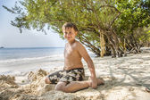Happy young boy is digging in the sand of the beach and constructing sand buildings — Stock Photo