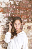 Woman in white shirt with old brick wall background — Stock Photo