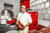 Butcher prepares fresh sausage — Stock Photo
