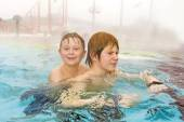 Brothers are swimming in the outside area of a thermic pool in W — Stock Photo