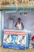 Laundry man poses at his shop with poster — Stock Photo