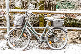 Snow codered bicycle leaning at a handrail — Stock Photo