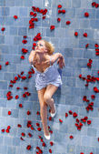 Woman poses in a bed of roses in the pool — Stock Photo