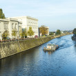 Постер, плакат: Berlins buildings and a boat shipping at the river Spree