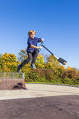 Child going airborne with  scooter — Stock Photo