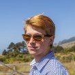 Cool teenage boy with sunglasses walks happy on the meadow — Stock Photo #68730411