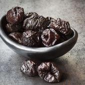 Prunes in Black Bowl — Stock Photo
